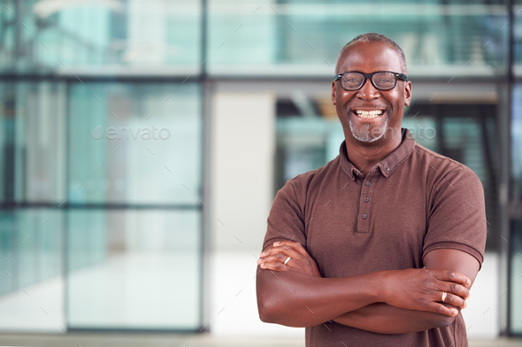 Portrait Of Smiling Mature Businessman Standing In Lobby Of Busy Modern Office - Stock Photo - Images