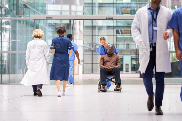 Female Nurse Wearing Scrubs Wheeling Patient In Wheelchair Through Lobby Of Modern Hospital Building - Stock Photo - Images