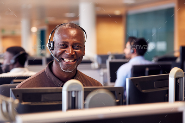 Portrait Of Mature Businessman Wearing Telephone Headset Working In Customer Services Department - Stock Photo - Images