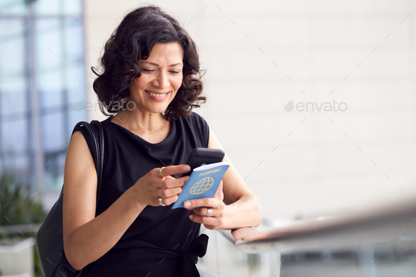 Mature Businesswoman With Passport In Airport Departure Lounge Using Mobile Phone - Stock Photo - Images