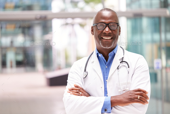 Portrait Of Male Doctor With Stethoscope Wearing White Coat Standing In Modern Hospital Building - Stock Photo - Images