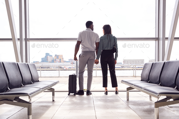 Rear View Of Business Couple With Luggage Standing By Window In Airport Departure Lounge - Stock Photo - Images