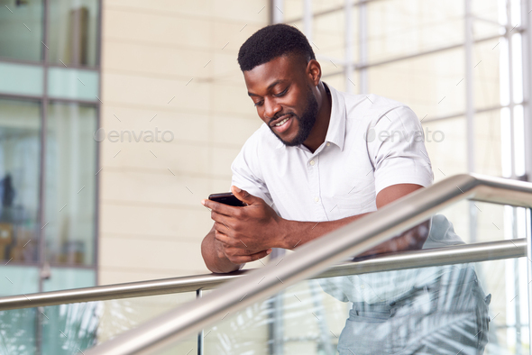 Businessman Standing In Lobby Of Modern Office Using Mobile Phone - Stock Photo - Images