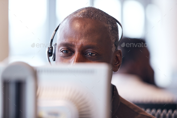 Mature Businessman Wearing Telephone Headset Talking To Caller In Customer Services Department - Stock Photo - Images