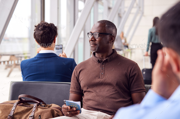 Male Passenger Sitting In Airport Departure Lounge Holding Passport - Stock Photo - Images