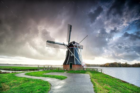 dark dramatic rainy cloud over Dutch windmill - Stock Photo - Images