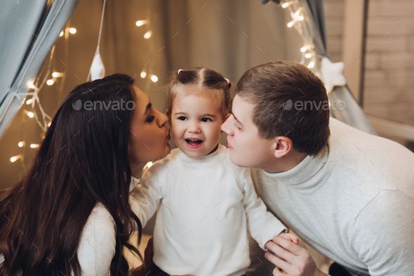 Loving parents kissing their cute daughter in cheeks - Stock Photo - Images