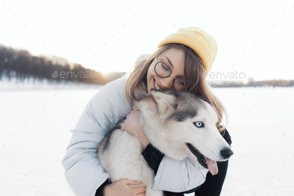 Happy young girl playing with siberian husky dog in winter park - Stock Photo - Images