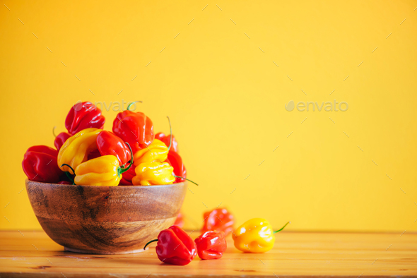Colorful scotch bonnet chili peppers in wooden bowl over orange background. Copy space - Stock Photo - Images