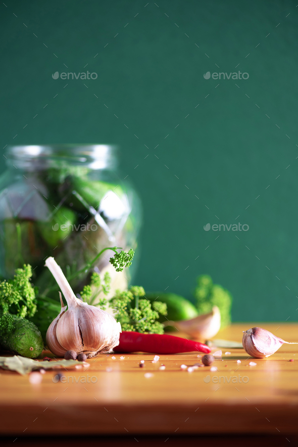 Ingredients, spices and herbs for canning cucumbers on green background. Copy space. Dill flowers - Stock Photo - Images
