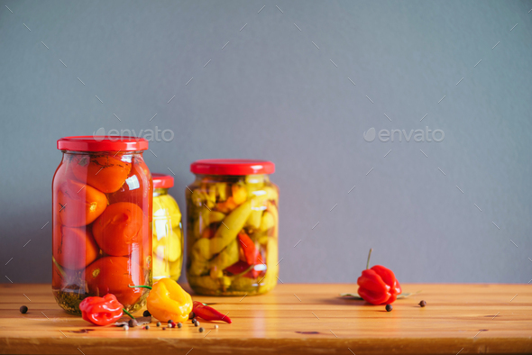 Preserved vegetables in glass jars on wooden background. Copy space. Healthy fermented food concept - Stock Photo - Images