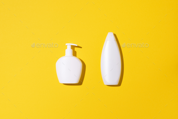 Shampoo and soap bottles on yellow background. Top view. Flat lay. Copy space - Stock Photo - Images