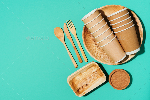 Disposable tableware from natural materials. Bamboo plates, wooden spoon, fork, knife, craft paper - Stock Photo - Images