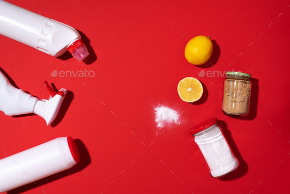 Baking soda, lemon and mustard powder against household chemicals products over red background. Top - Stock Photo - Images