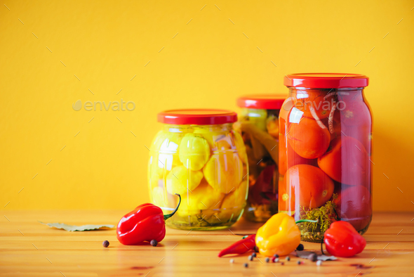 Preserved vegetables in glass jars on orange background. Copy space. Healthy fermented food concept - Stock Photo - Images