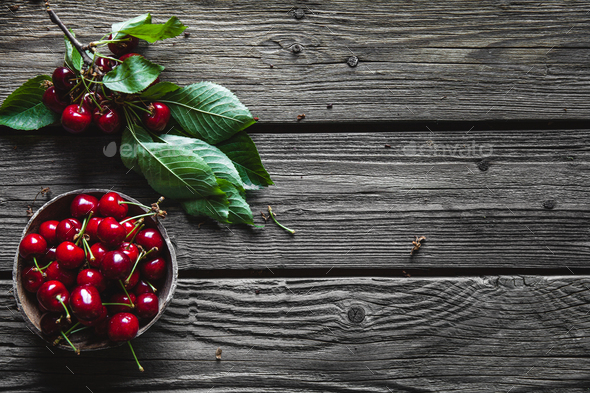 Wooden background with several delicious cherries on green leaves - Stock Photo - Images