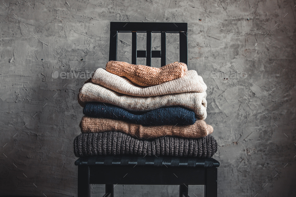 a stack of knitted warm cozy sweaters , on a chair by the gray wall. autumn, winter concept - Stock Photo - Images