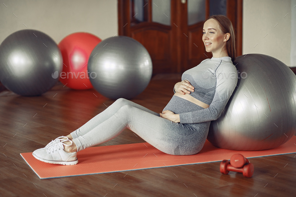 Pregnant woman training in a gym - Stock Photo - Images