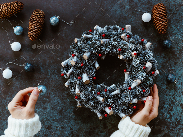 Girl's hands in a winter white sweater hold a Christmas holiday wreath - Stock Photo - Images