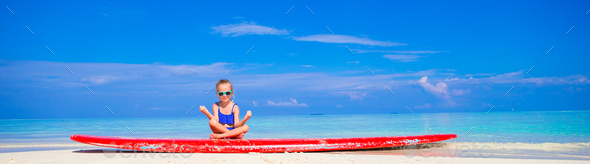Little girl in yoga position meditating on surfboard - Stock Photo - Images