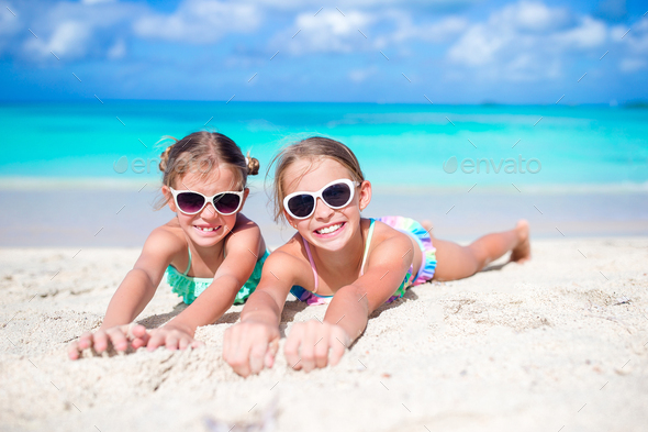 Close up little girls on sandy beach. Happy kids lying on warm white sand - Stock Photo - Images