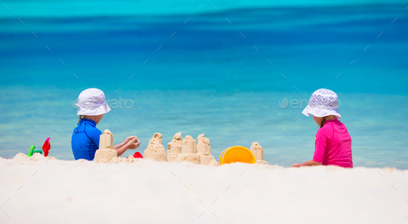 Little girls playing with beach toys during tropical vacation - Stock Photo - Images