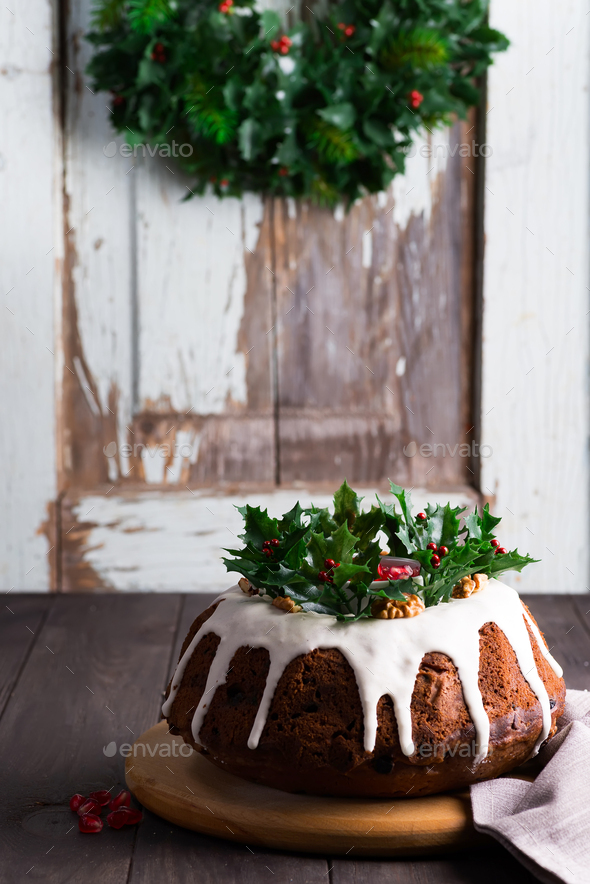 Christmas homebaked chocolate cake decorated with white icing and pomegranate kernels against the - Stock Photo - Images