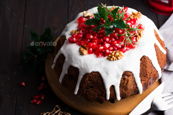 Christmas chocolate cake with white icing and pomegranate kernels on a wooden dark background with - Stock Photo - Images