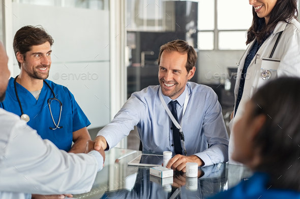 Salesman shaking hands with doctor - Stock Photo - Images