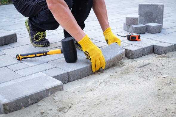 The master in yellow gloves lays paving stones - Stock Photo - Images