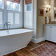 Luxury bathroom with large white tub, beautiful cabinets, and shiplap walls. - PhotoDune Item for Sale