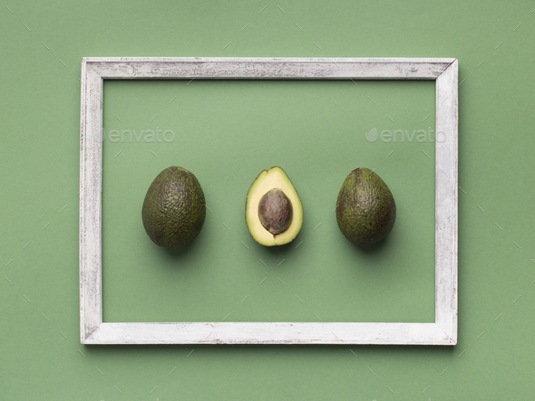 Avocado inside wooden border in minimalism style on green - Stock Photo - Images