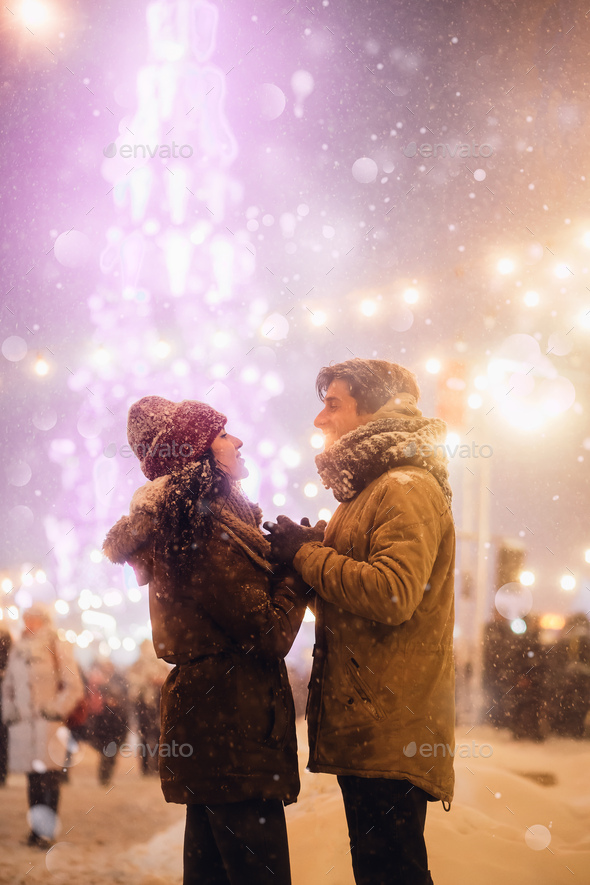 Couple Holding Hands Standing Against Christmas Tree In Night City - Stock Photo - Images