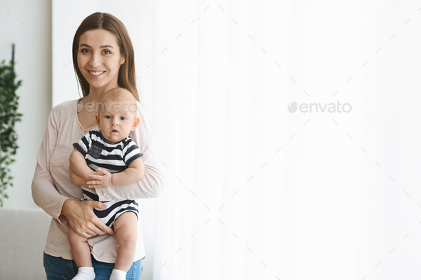 Pretty woman holding newborn baby in arms, standing near window - Stock Photo - Images