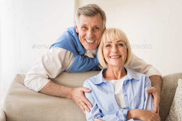Lovely mature man embracing wife and smiling to camera - Stock Photo - Images