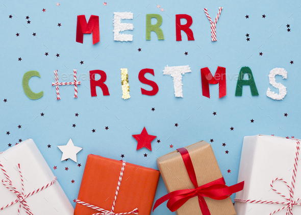 Merry Christmas wishes and gifts in boxes on blue background - Stock Photo - Images