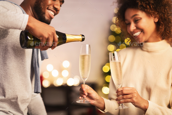 Husband pouring champagne, celebrating Christmas with wife - Stock Photo - Images