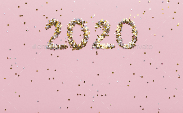 Super glowing background with gold 2020 of confetti on pink - Stock Photo - Images