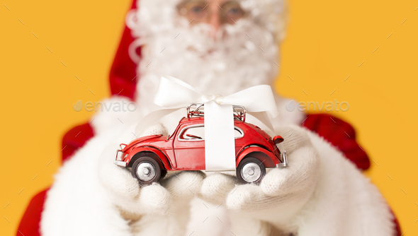 Blurred Santa Claus suggesting toy car with present bow - Stock Photo - Images