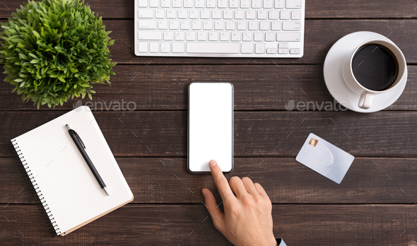 Unrecognizable office employee using smartphone with blank screen at workplace - Stock Photo - Images