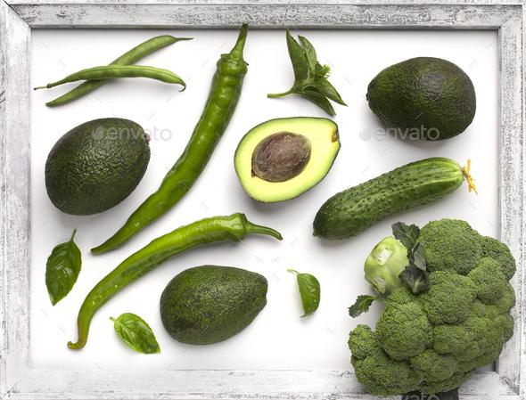 Green organic vegetables inside wooden border on white - Stock Photo - Images