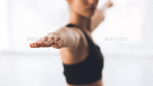 Woman exercising yoga in warrior pose, focus on hand - Stock Photo - Images
