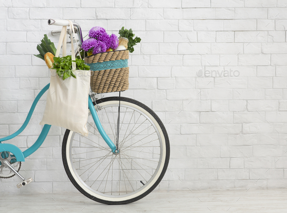 Bicycle with wildflowers and organic food over white bricks wall - Stock Photo - Images