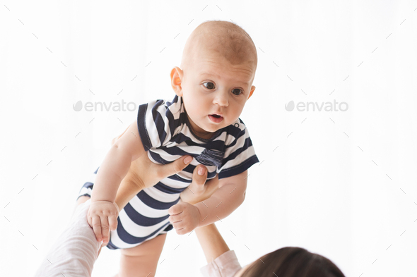 Closeup portrait of lovely baby lifted in air by mother - Stock Photo - Images