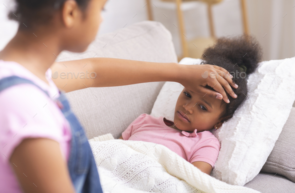 African american teen girl touching her sick little sister's forehead - Stock Photo - Images