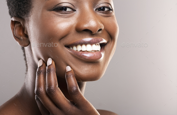 Beautiful black girl with perfect smooth skin touching her face - Stock Photo - Images