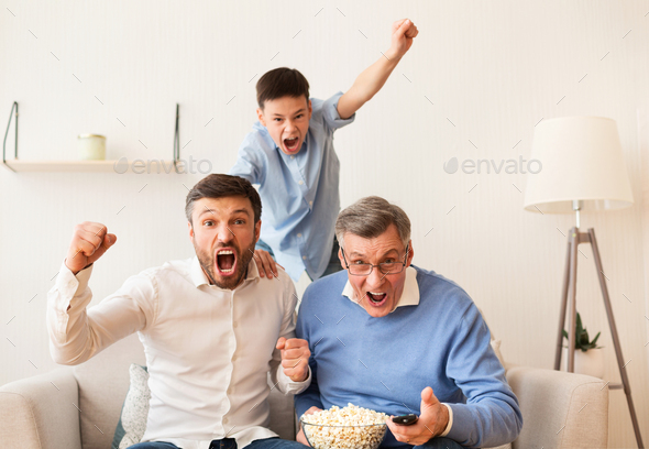 Grandfather, Father And Son Watching Football Match On TV Indoor - Stock Photo - Images
