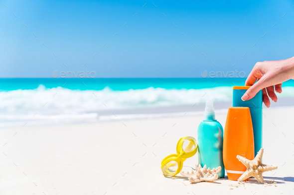 suntan lotion bottles and starfish at the beach - Stock Photo - Images