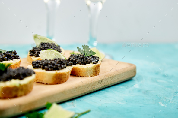 Sturgeon black caviar in wooden bowl, sandwiches and champagne on white background copy space. - Stock Photo - Images