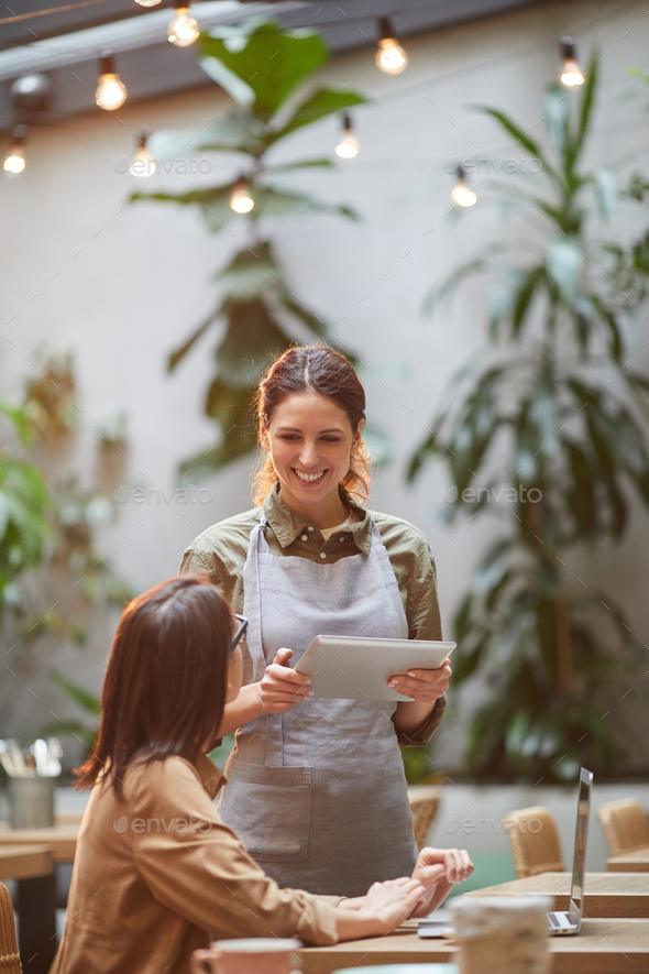 Cheerful Waitress Talking to Client at Cafe Terrace - Stock Photo - Images
